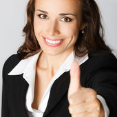 Businesswoman with thumbs up, over gray — Stock Photo
