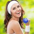 Stock Photo: Womexercising with dumbbell, outdoors