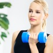 Young happy smiling woman with dumbbells, indoors — Stock Photo
