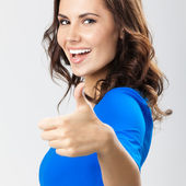 Young woman with thumbs up gesture, over grey — Stock Photo