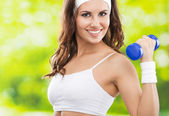 Woman exercising with dumbbell, outdoors — Stock Photo