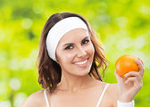 Woman in fitness wear with orange, outdoors — Stock Photo