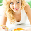 Cheerful woman eating cereal muslin  — Stock Photo #28566605