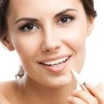 улыбается женщина, применяя тональный крем на лице, изолированные — Стоковое фото
