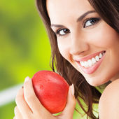 Young woman with red apple, outdoors — Stock Photo