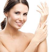 žena dotýká kůže nebo použitím krém, izolované — Stock fotografie