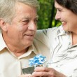 Mature couple embracing in park with gift — Stock Photo #29176477