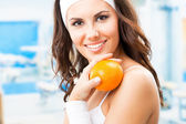 Woman with orange, at fitness center — Stock Photo