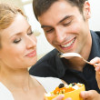 Cheerful young couple with vegetarian salad at home — Stock Photo