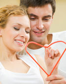 Young amorous couple with heart symbol — Stock Photo