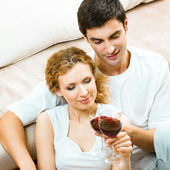 Cheerful couple with glasses of redwine — Stock Photo