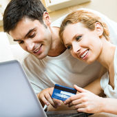 Cheerful couple paying by plastic card — Photo