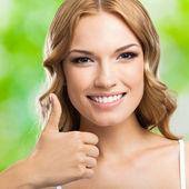 Šťastná žena s palce gesto, venkovní — Stock fotografie