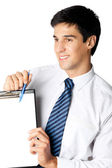 Happy smiling young business man showing blank clipboard — Stock Photo