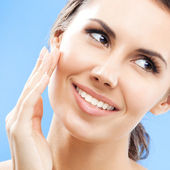 Woman touching skin or applying cream, over blue — Stock Photo