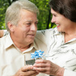 Mature couple embracing in park with gift — Stock Photo