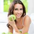 Young happy smiling woman with apples, indoors — Stock Photo
