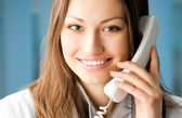 Young doctor on phone, at office — Stock Photo