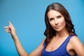 Woman showing copyspace or something, over blue — Foto de Stock