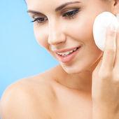 Mladá žena čištění kůže vatový tampon, nad modrá — Stock fotografie