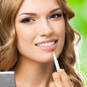 Smiling woman with make up brush, outdoor — Stock Photo
