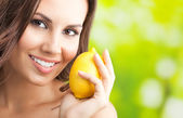 Young happy smiling woman with lemon, outdoors — Stock Photo