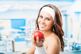 Woman with apple, at fitness center — Stock Photo