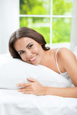 Young beautiful woman waking up, at bedroom — Stock Photo