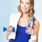 Young woman with water, dumbbell and towel — Foto de Stock