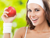 Woman in fitness wear with apple, outdoors — Stock Photo