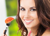 Smiling young woman eating tomato, outdoors — Stock Photo