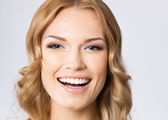Young cheerful smiling woman, on gray  — Stock Photo
