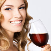 Young happy woman with glass of red wine, on gray — Stock Photo