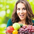Stock Photo: Womwith plate of fruits, outdoors