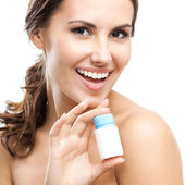 Smiling woman showing medical drug, isolated — Stockfoto