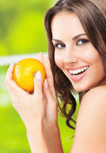 Young woman with orange, outdoors — Stock Photo