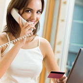 Woman with phone, paying by plastic card — Stock Photo