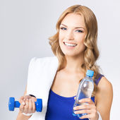 Young woman with water, dumbbell and towel — Stock Photo