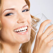 Young woman drinking water, on gray — Stock Photo