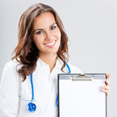 Female doctor showing blank clipboard, on grey — Stock Photo