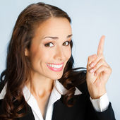 Businesswoman showing blank area for sign or copyspase, over blu — Stock Photo