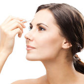Smiling woman applying concealer on face, isolated  — Stock Photo
