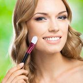 Mujer sonriente con maquillaje cepillo, al aire libre — Foto de Stock