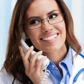 Smiling young doctor on phone — Stock fotografie