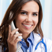 Smiling young doctor on phone, at office — Stockfoto