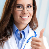 Doctor showing thumbs up gesture, at office — Stock Photo