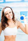Woman exercising with dumbbell, at fitness center — Stok fotoğraf