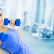 Young happy woman doing fitness exercise, at gym — Stock Photo #47313719