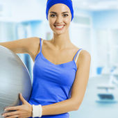 Young happy woman with fitness ball, at gym — Stock Photo
