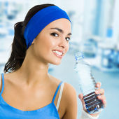 Woman in sportswear drinking water, at gym — Stock Photo